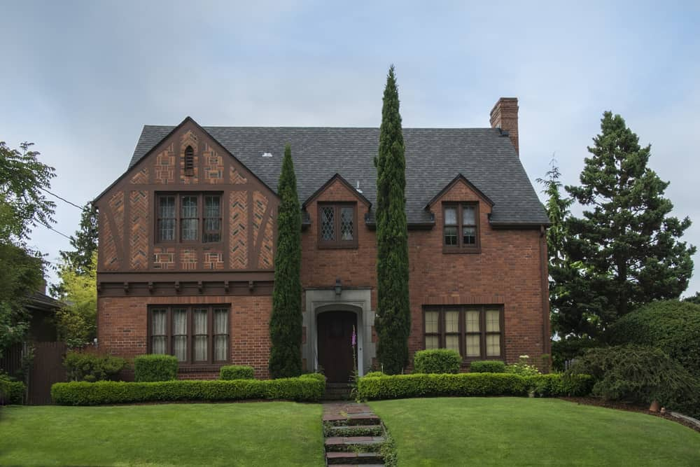 Older red brick home in Tudor Revival style with boxwood hedge iin front. Very nice, stately home.