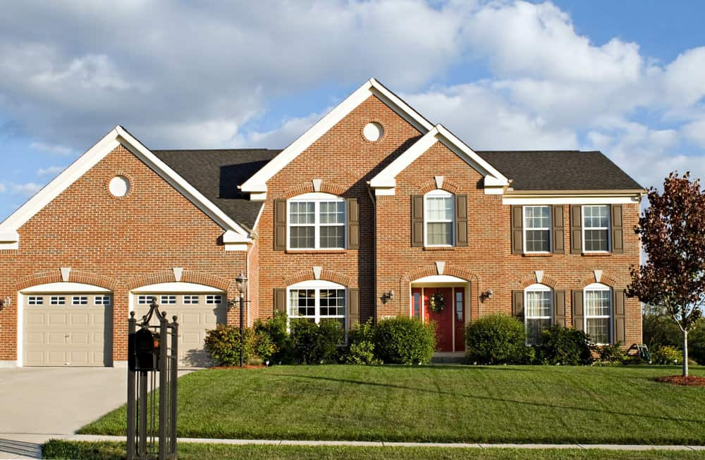 Red brick home with bright red door and two car garage in suburb.