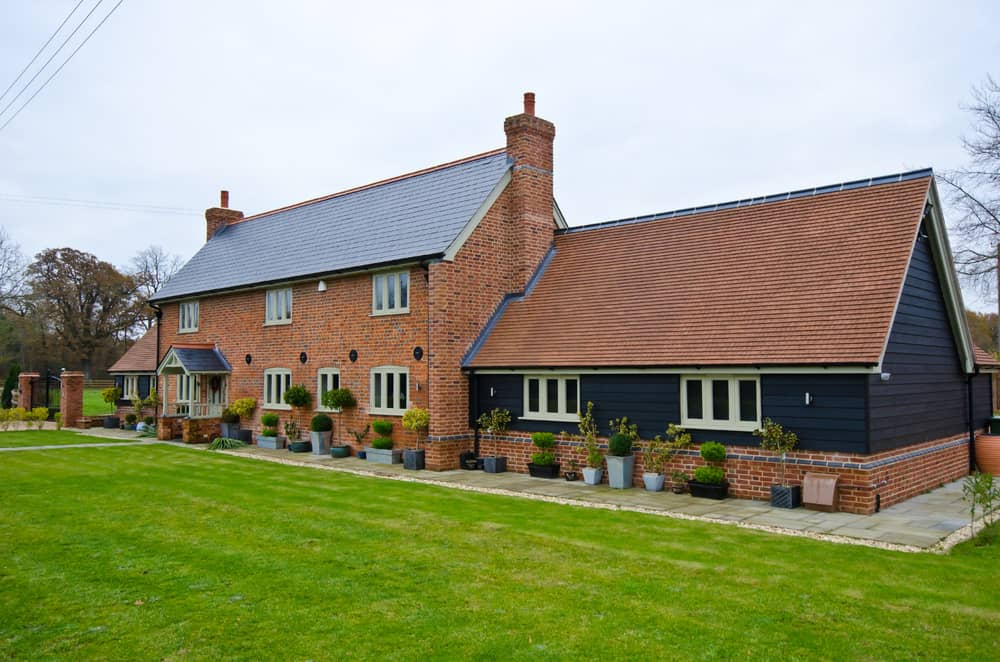 English country home with red brick facade set on large property with spectacular lawn.