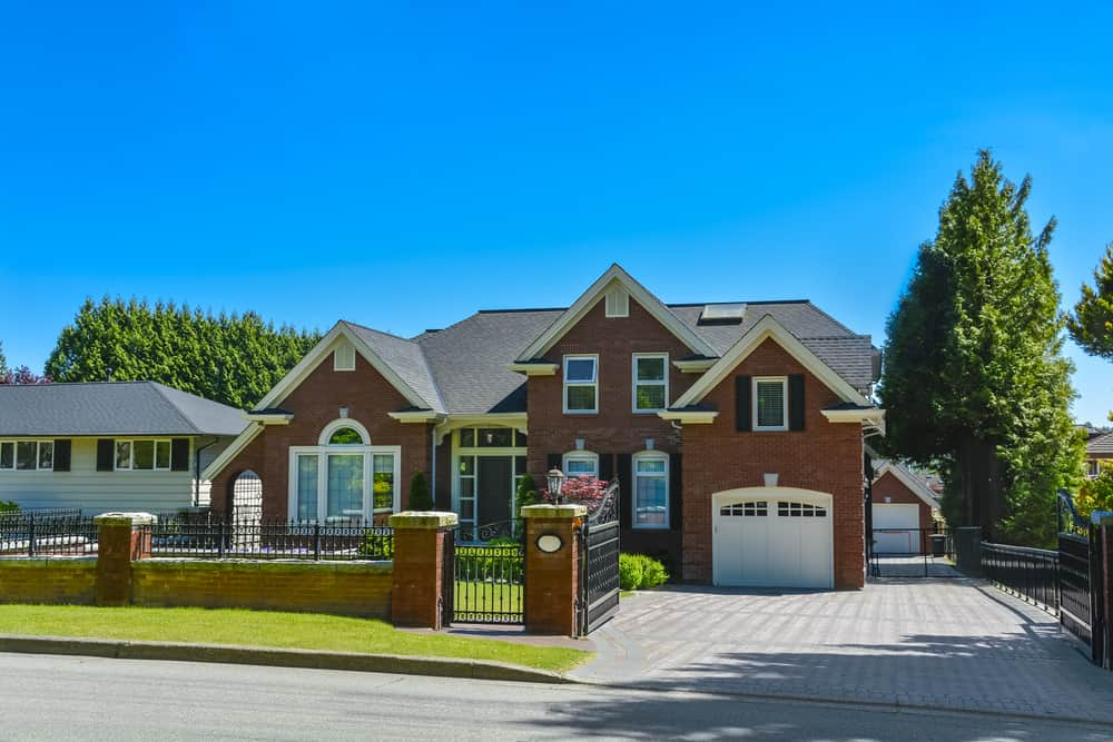 New suburban home with white garage door, shutters on windows and red brick exterior along with red brick front fence.