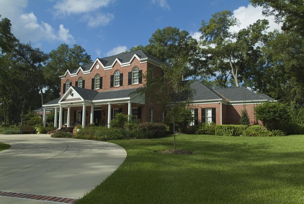 Stately two story home with white columns, black shutters and red brick at the end of a circular driveway.