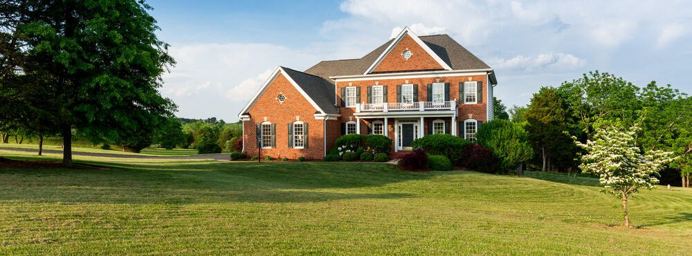 Incredible country home with red brick exterior set in huge sprawling lawn and scattered trees.