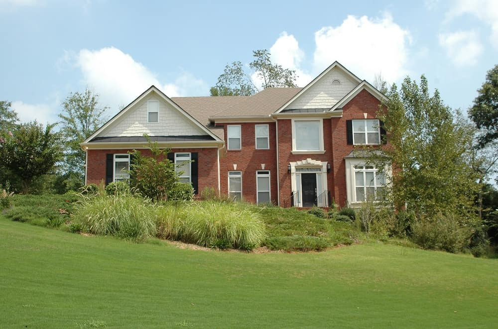 New home with red brick, white trim and black exterior shutters. Large sloping front yard with ornamental grasses and large lawn.
