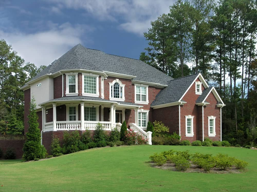 Stunning red brick home with prominent white trim. Rounded corner with round veranda.