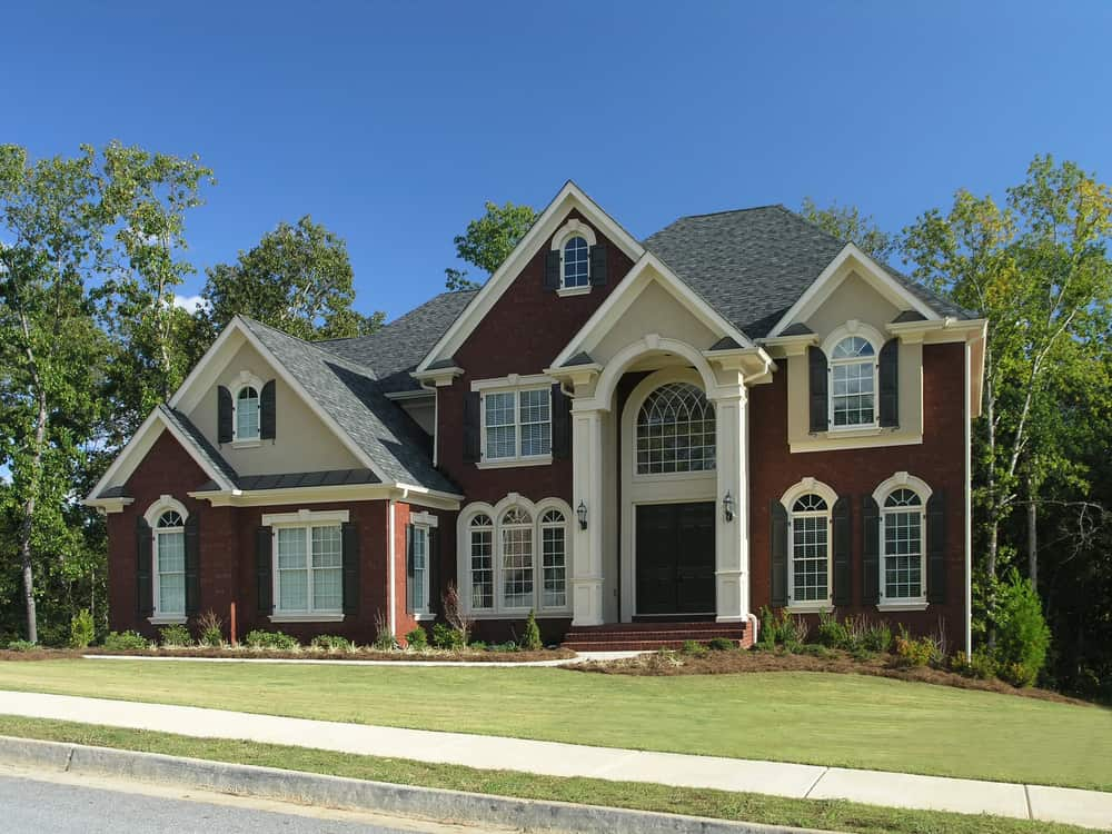 New large suburban red brick home with arched windows, side garage, grey shingles and gardens in the front yard.