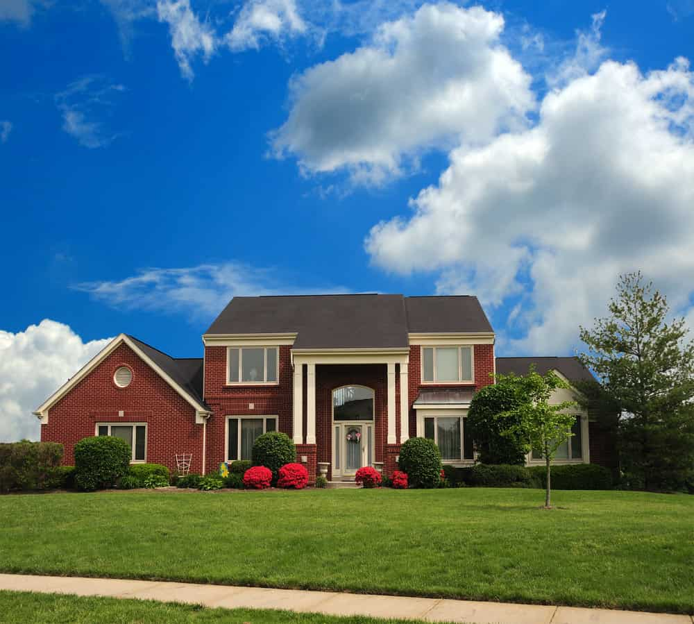 2 story symmetrical home with bright red brick and columns flanking the front door.
