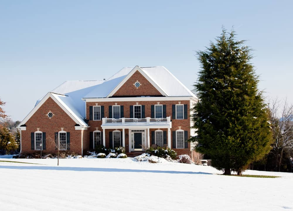 Georgian style red brick home on large property with snow covered ground.