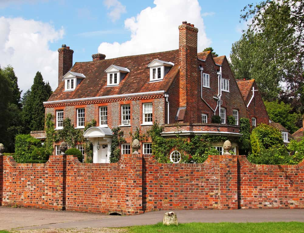 Old red brick mansion with white door surrounded by tall red brick fence.