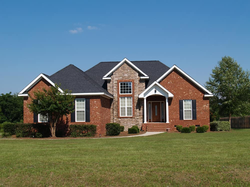 Suburban home with red brick and stone facade.