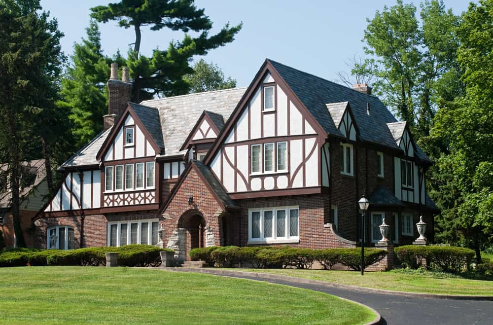 Stunning Tudor Revival style home with red brick lower exterior topped with the classic half-timber on white. circular driveway and manicured property makes this a really great looking estate.