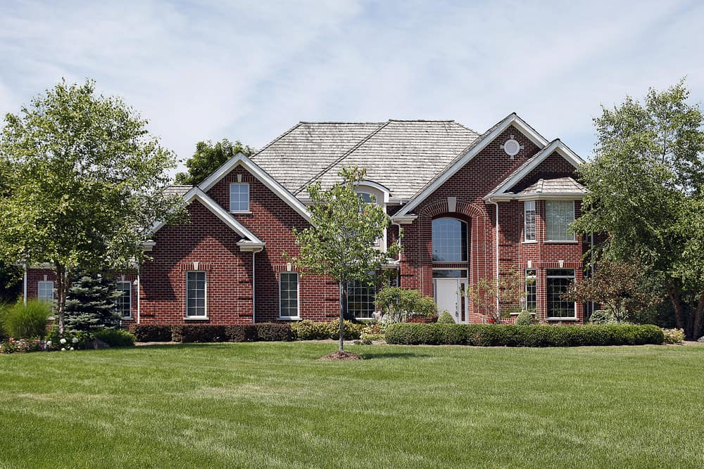 Sprawling two story red brick mansion on large property with huge lawn and young trees.