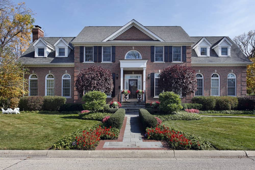 Luxurious red brick mansion with arched windows flanking the main central structure.