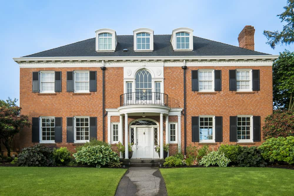 Stately two story red brick house with dormers, shutters, columns... the whole shebang.