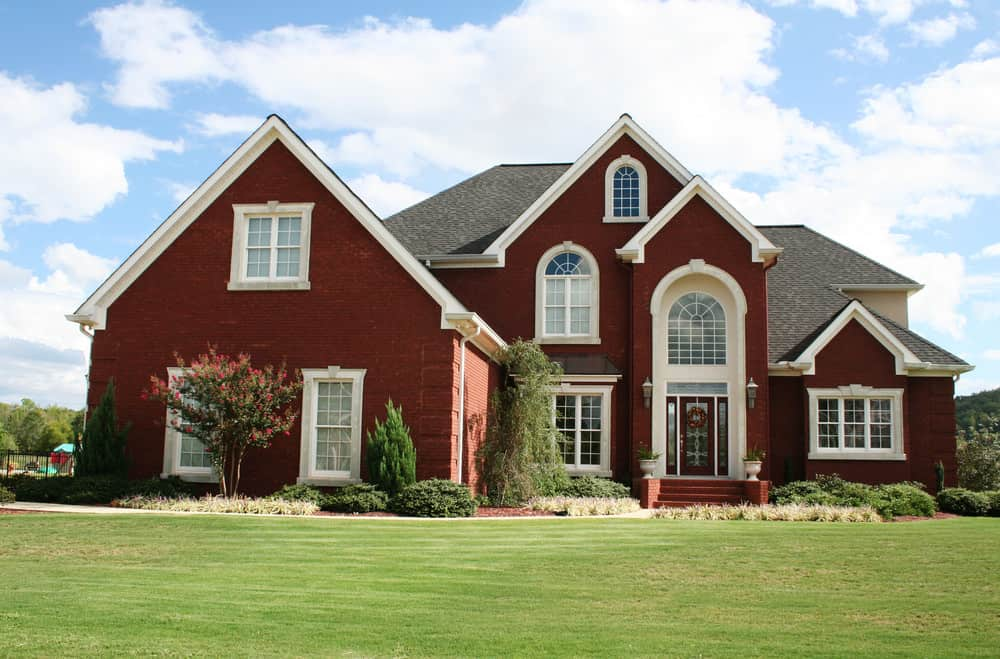 Shield your eyes... bright, bright red brick with white trim house. Large, towering home with red brick stairs to the imposing front door.