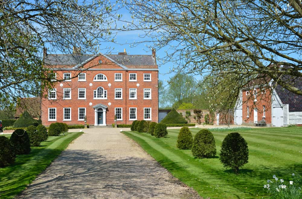 Grand red brick manor home in England with long driveway.