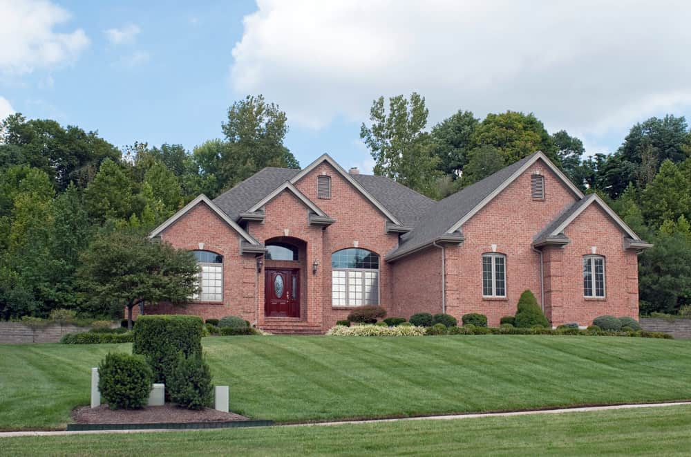 Another suburban house with red brick exterior set on gorgeous lawn and greenbelt backyard.