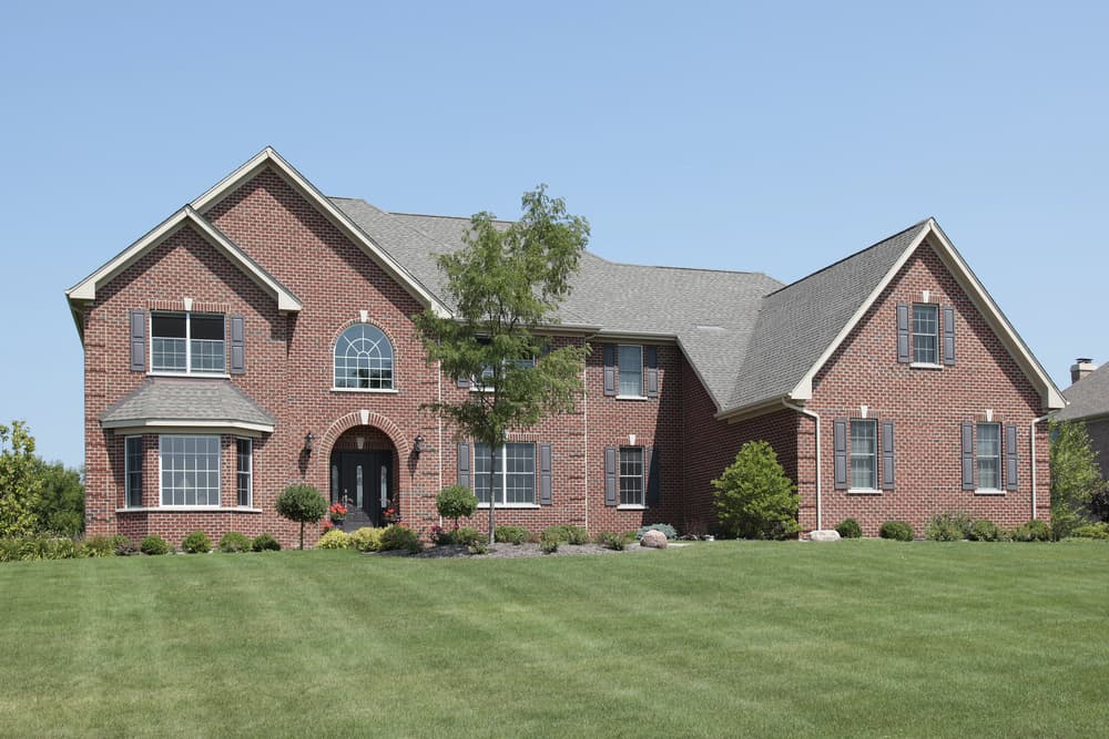 Red brick McMansion with large front yard.