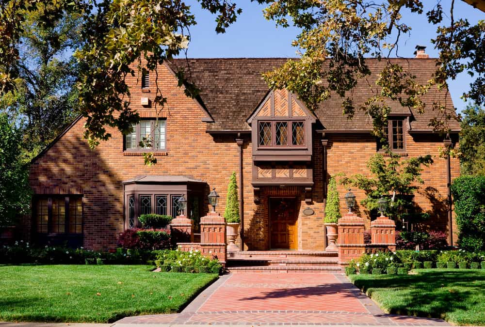 Old Tudor Revival style red brick home with stunning red brick walkway to the front door. That walkway is simply fabulous.