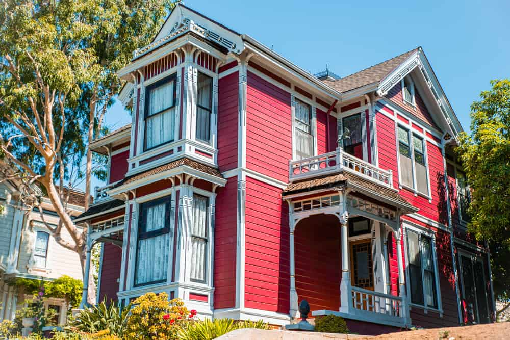 Bright red Victorian style home with large prominent front windows for both floors.