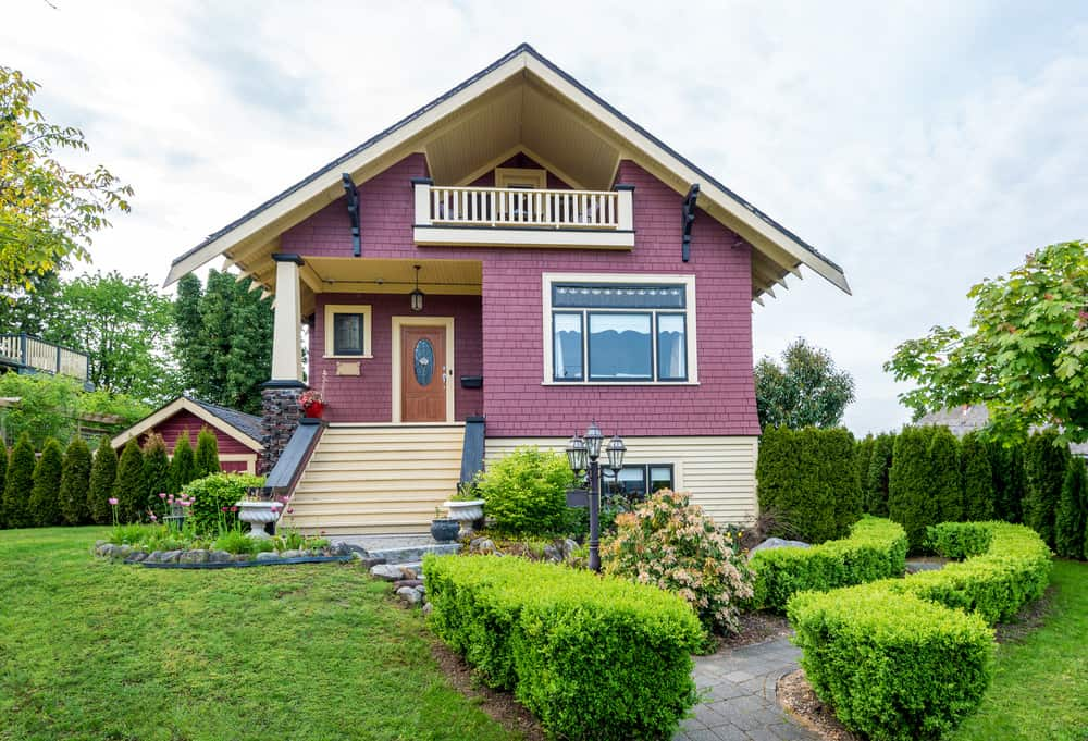 Bungalow style home with purple red shingle exterior combined with soft yellow exterior. Interesting covered balcony under the gable peak overlooks the front yard.