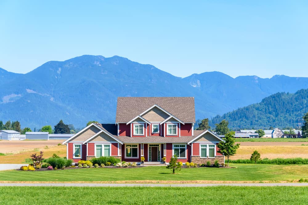 Handsome red home on large farm with mountains in the background. The area under the multiple gables of the roof is beige, which I don't think works well. I don't care for the red and beige contrast.