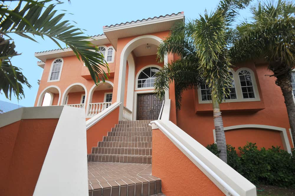 Salmon colored beach mansion with stucco exterior. White trim contrasts nicely with this tropical home. Long set of brown tile stairs leads to large double wide wood front doors situated under an arched window.