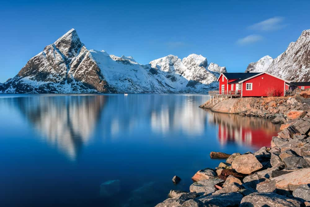 Red home on rocky property next to a Norwegian fjord. Stunning photo of the fjord with rising snow-covered rocky mountains. I'd love to go there some day.