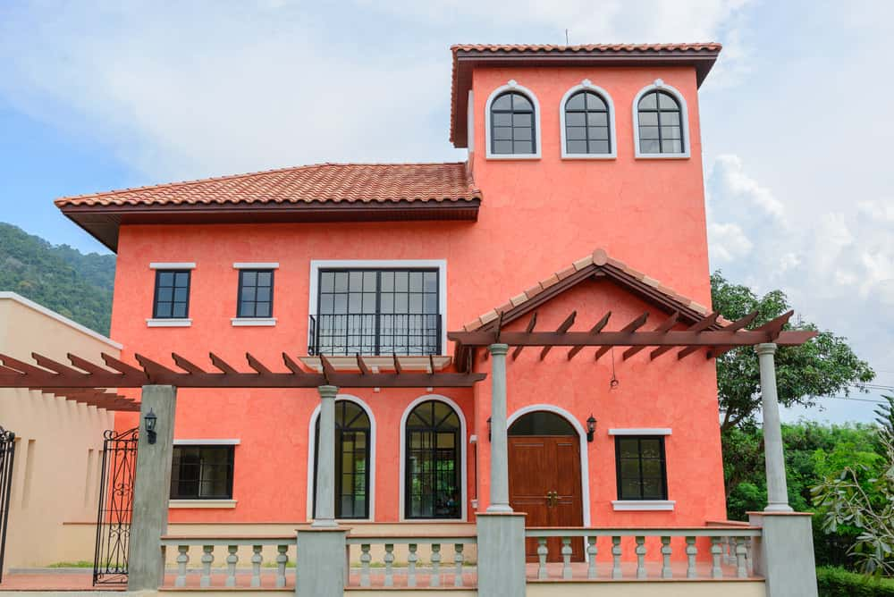 Pink red tropical home with a tower room.