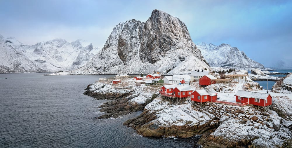 Aerial view of a stunning Norwegian fishing village peppered with red homes.