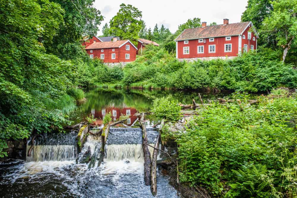 View of several red exterior homes in Sweden next to a small river surrounded by lush vegetation.
