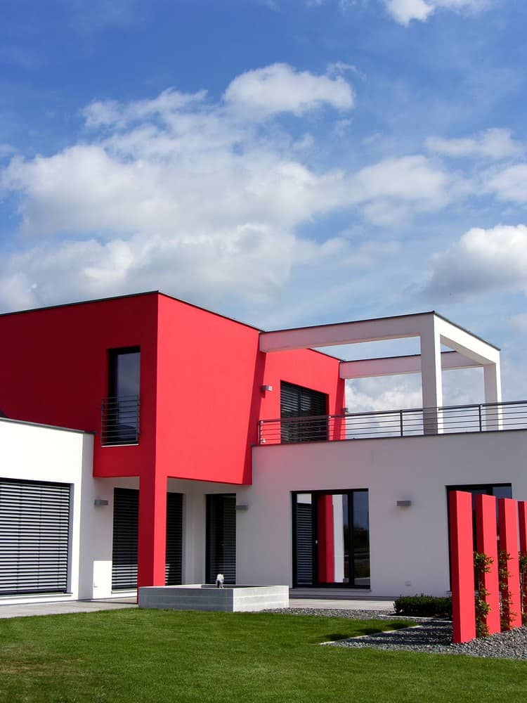Modern home with red and white exterior. This attractive cube style home includes roof-top balcony and red sculpture fence in the front yard.