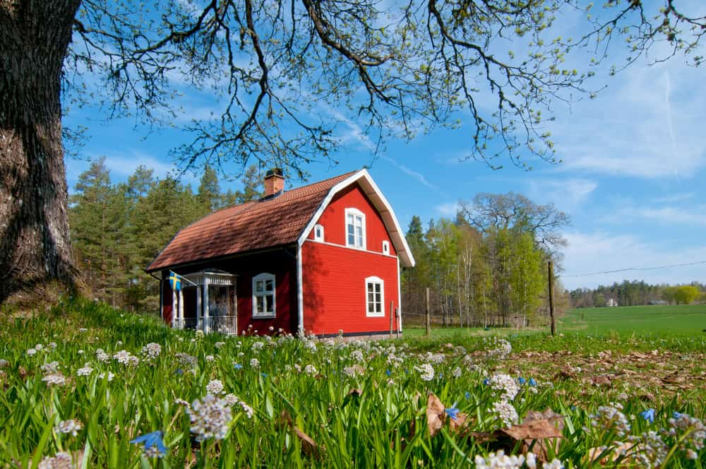 Quaint Swedish red home with gambrel roof surrounded by trees and meadow.