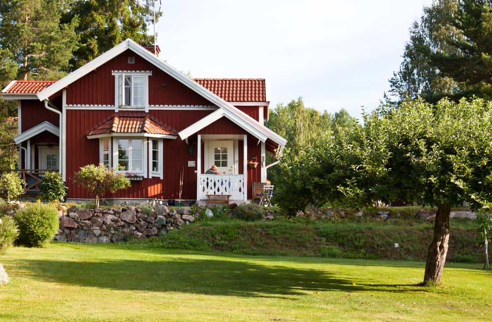 Another classic Swedish red home with white trim on country property with lawn, trees and surrounded by forrest.