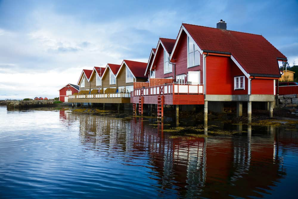 Red houses on stilts built on the water. The homes are built in an old design but are new with the terrific picture window and contemporary deck railing jutting out over the water.