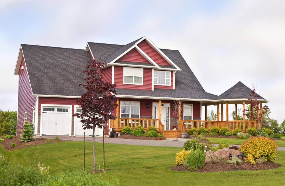 Red exterior home with white trim and white carriage garage doors. The red and white is tempered with a natural wood railing porch and gazebo that extends off the home's veranda.