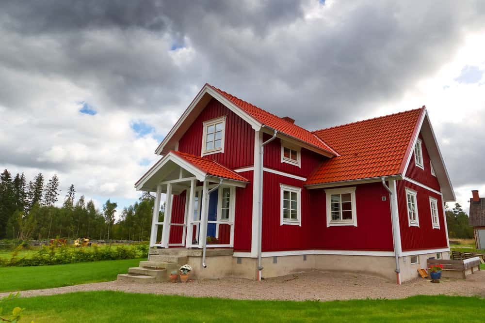 Another red and white Swedish country home with red tile roof. This home sits on a large open property.