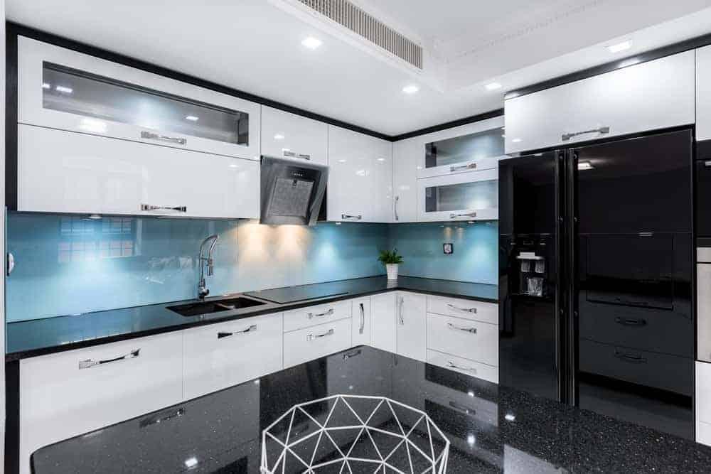Glossy black refrigerator in a modern glossy white kitchen.