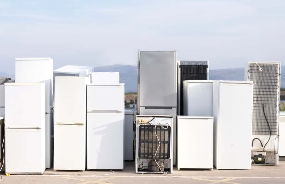 A pile of old and used refrigerator in a junk yard.