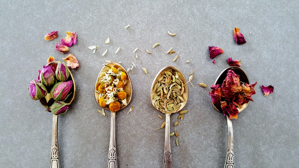 Flat lay of Indian crumbled roses, fennel seeds, chamomile and Moroccan roses on gray background.