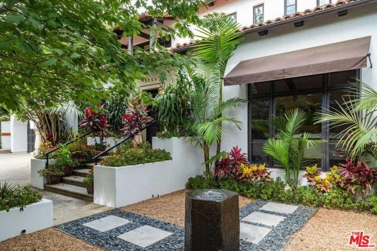 The courtyard features amazing pathway and colorful flowers and healthy green plants.