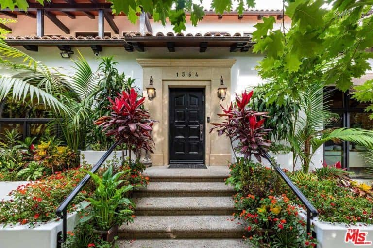The home features a very welcoming entrance with plants and flowers on the side.