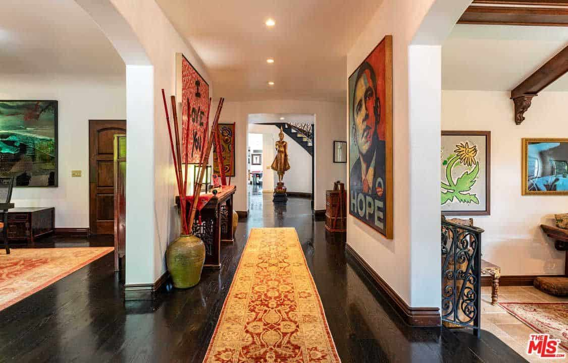 The home's entry features an elegant rug on a hardwood espresso flooring with portrait wall decor and recessed ceiling lights.