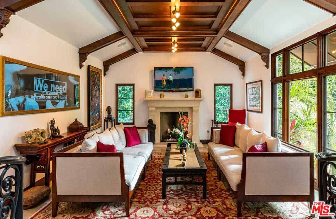This Mediterranean home boasts a lovely rug and a glamorous ceiling with beams lighted by beautiful track lights. The pair of couches look perfect together with the walls and the fireplace.