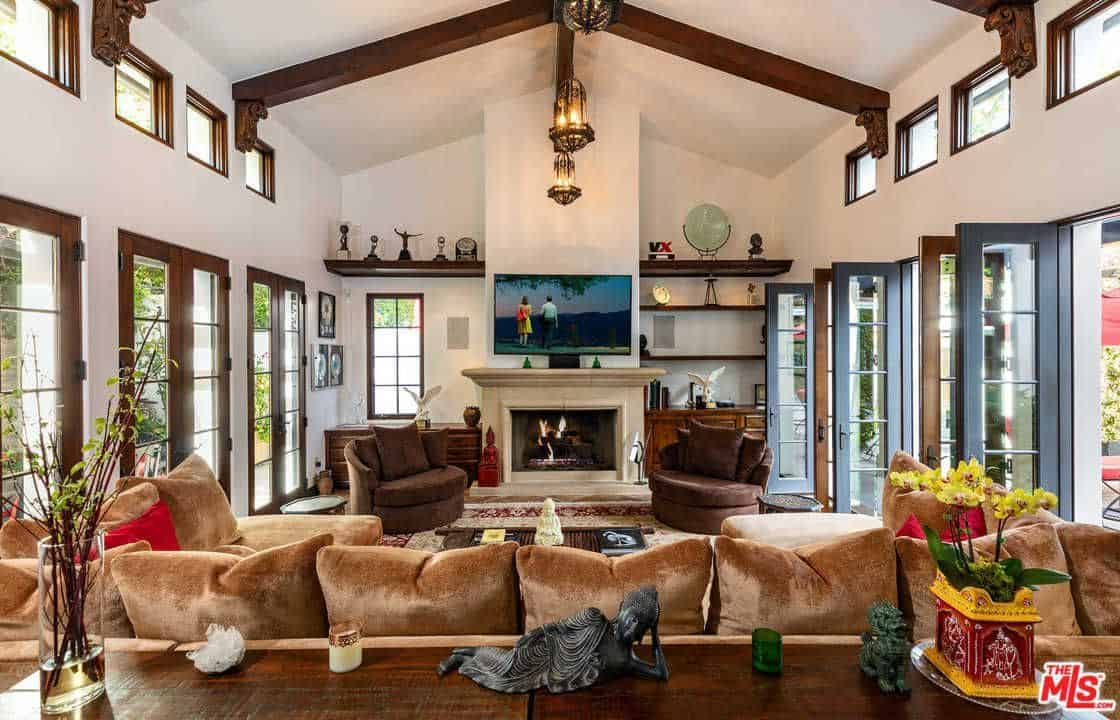 Large Mediterranean home with elegant sofa set and a fireplace with TV on top of it. The lighting set on the high vaulted ceiling with beams looks stunning.