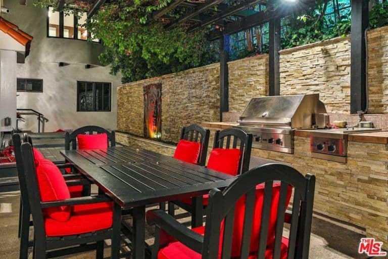The outdoor kitchen has its own dining area equipped by classy table and chairs set.