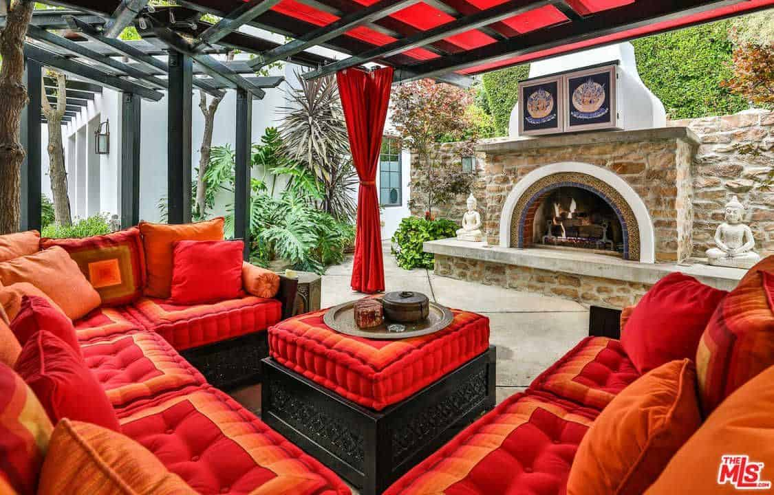 This classy patio offers a red-themed seats, table and curtains. There's a fireplace in front of the area.