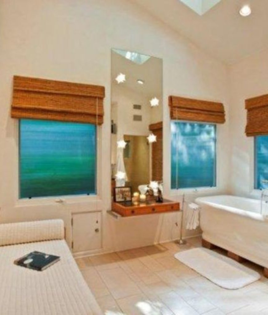 The bathroom is complete with a soaking tub, shower room and a bench sitting with a skylight.