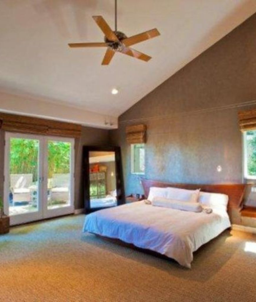 The bedroom boasts a full carpet flooring and and a queen sized bed along with recessed lights on a shed ceiling. There's also a doorway leading to the house's outdoor.