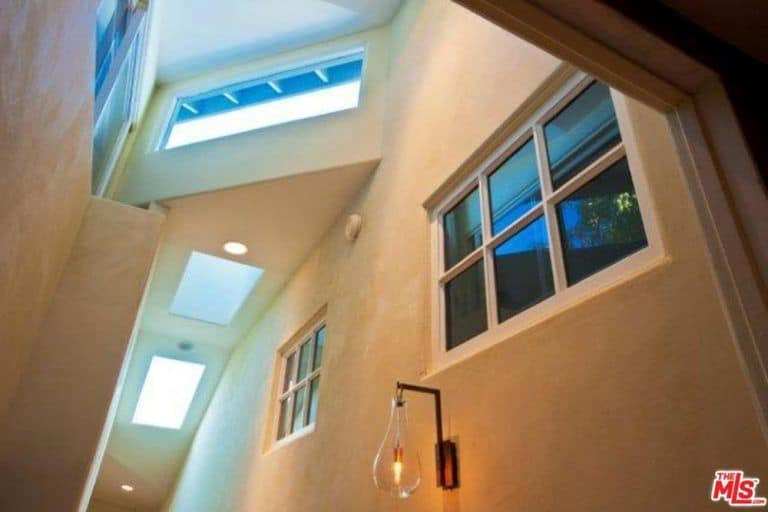 The hallway features a wall lighting, recessed lights and a skylight.