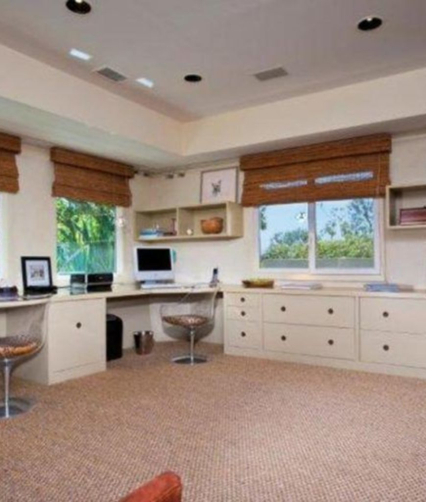 The home office has two built-in desks and multiple cabinets along with glass windows equipped by a classy blinds.